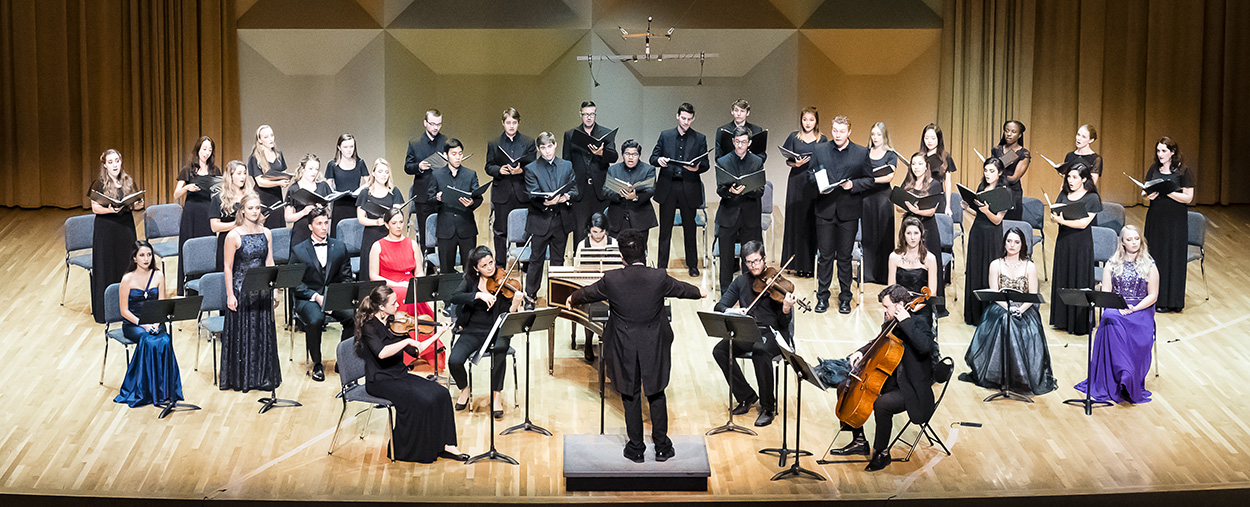 Musicians with string instruments and a choir perform live