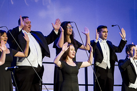 Choral Ensemble sings into microphones with their hands held up
