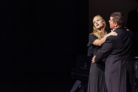 A woman and a man under the spotlight singing